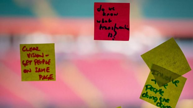"""Post it notes on a window at a workshop in Cardiff's Transforming Together - one reads """"clear vision - get people on the same page"""""""