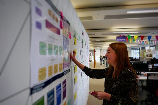 A picture of Georgie Baker putting a post it note on a poster of the bigger picture.
