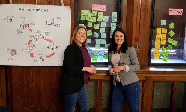 Two people - including the author, Rebecca Herbert - are standing in front of a wall. On the left of the wall is a poster titled 'plan, do, study, act' - in the middle are post its under a heading 'To Do' - and on the right are post its under the heading 'Doing'