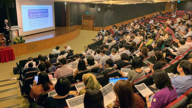 A lecture hall at the Civil Service College in Singapore - rows of students are looking at printouts of the 7 Lenses Maturity Matrix, while Naomi Stanford stands on the stage, on the left of the picture, presenting the same material.